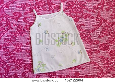 Light Sundress with green and blue little flowers thin spaghetti straps for newborns .Things for babies on a pink blanket. Clothes for baby close up.
