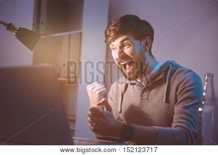 Happy victory. Delighted handsome young man winning a computer game and feeling happy about it while using a laptop.