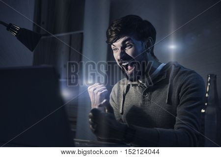 Involved in jubilation. Happy young handsome man playing computer game and winning it while using his laptop in the evening
