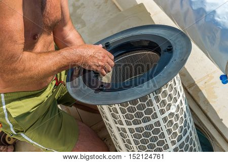 senior man change or check the cartridge pool filter