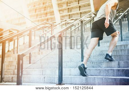 Before it started. Athletic active young man going to stadium climbing up the stairs before having training.