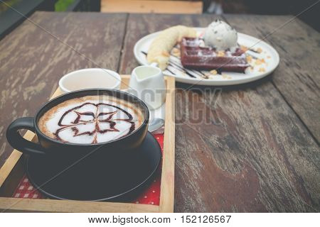 chocolate waffles with vanilla ice cream and banana served with hot coffee. chocolate waffles in cozy outdoor cafe.(selective focus vintage effect)