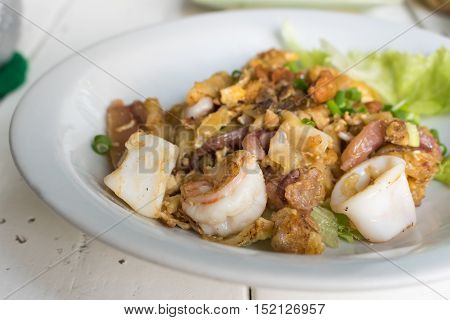 Thai food Stir fried rice noodle with chicken squid and shrimp in restaurant.