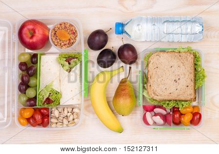 Food for lunch, lunchboxes with sandwiches, fruits, vegetables, and water, top view