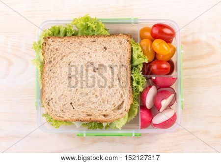 Sandwich in a lunchbox with tomatoes and radish, top view on a wooden table