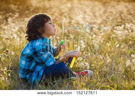 Little smiling boy playing soap bubbles in summer park outdoor.