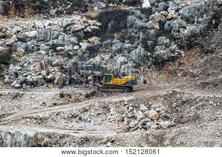 Yellow excavator machine working at gravel pit