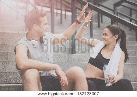 High five. Delighted happy active man and woman wearing sportswear and making cheerful gesture with their hands while waiting for training.