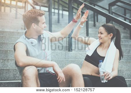 Enjoying sport. Active young delighted man and woman smiling to each other and giving a high five while waiting for training.