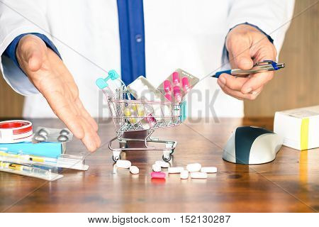 Pills and medicinal products inside shopping trolley - Doctor hands showing tablets and pharmaceutical package on wooden table - Concept of online medicines purchase risk