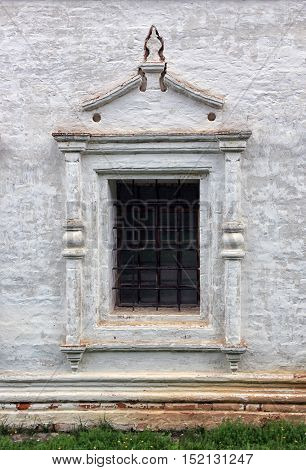 facade wall from plaster bricks with window with bars of old abandoned medieval russian orthodox church in old russian style in Russia