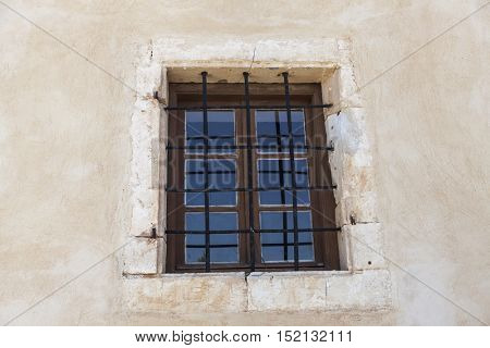 The old prison wall window with iron bars .