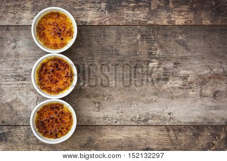 Creme brulee in ramekin on wooden table background
