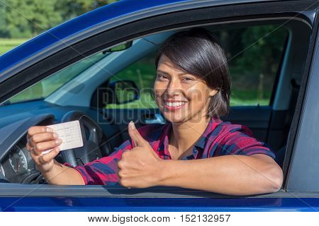 Young european woman showing driving license in car