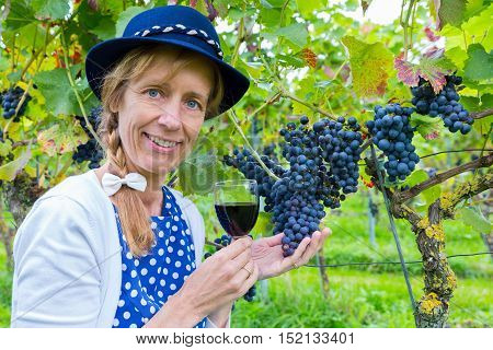 Woman in vineyard showing blue bunches of grapes and red wine