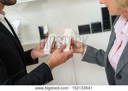 Close up of arms of salesman showing cosmetic product to mature woman. She is standing in store and smiling
