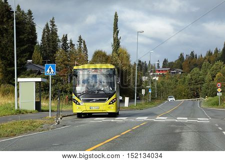 Tanem Norway - September 26 2015: Bus operated by Atb on line 47 with destination Trondheim at a bus stop in fron of a pedestrian crossing on road 704 in Tanem village.