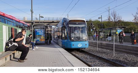Stockholm, Sweden - April 29, 2014: Passengers ready to embark the incomming tram at the Arstaberg tram stop.