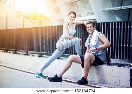 Sporty lifestyle. Beautiful woman and a handsome man smiling and relaxing together after exercising outdoors.
