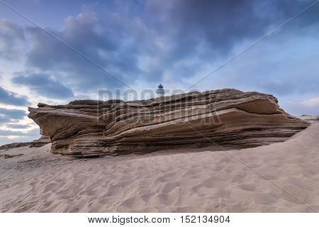 Large sandstone rock on the beach of Cape Trafalgar. With the Trafalgar lighthouse jutting. Costa de la Luz Cadiz Spain.