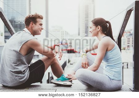 Cheerful relaxation. Beautiful slim woman and a handsome man smiling and looking at each other after working out in an urban setting.