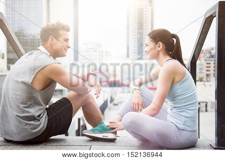 Pleasant relaxation. Beautiful young woman and a handsome fit man smiling at each other and relaxing after working out in an urban environment.