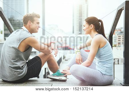 Happy relaxation together. Pretty young woman and a handsome athletic man sitting together and relaxing after working out in the city.