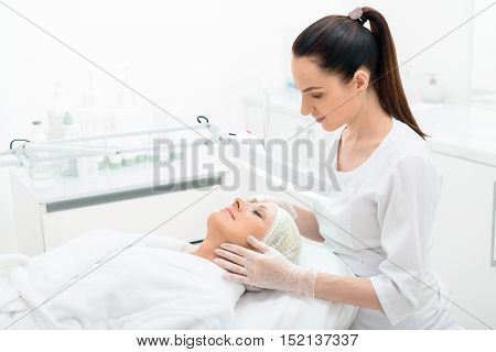 Professional beautician is examining female facial skin through lamp with concentration