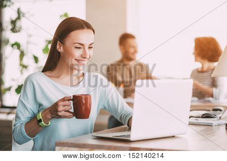 Get a nice rest. Pleasant delighted beautiful smiling woman drinking coffee and using laptop while her colleagues sitting at the table in the background