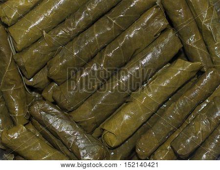 Wrap stuffed Grape leaves Dolmas. Food texture as background, Lebanese and Greek cuisine. Closeup.