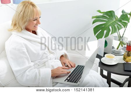 Serene mature woman is using laptop and smiling. She is sitting on armchair with relaxation and wearing bathrobe