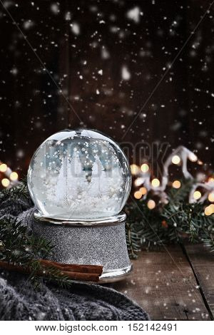 Rustic image of a snow globe surrounded by pine branches cinnamon sticks and a warm gray scarf with gently falling snow flakes.