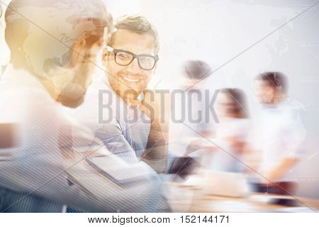 Worldwide business connection. Double exposure of blurred group of people and bearded businessman smiling to his partner behind worldwide interface.