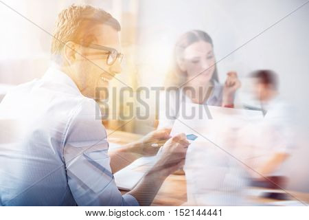 Sharing ideas. Back view of bearded man giving document to his partner during business meeting on blurred double exposed background.