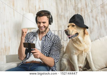 I won, happy guy cheering with smartphone in hands while dog looking at him indoors