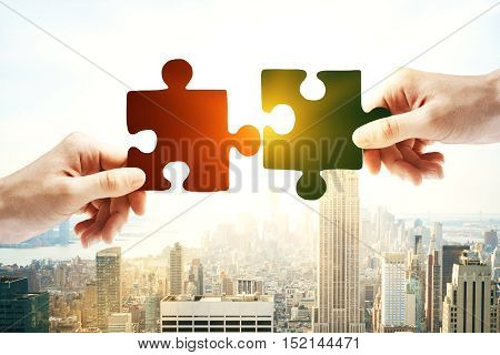 Hands putting puzzle piece together on bright city background with sunlight. Partnership concept