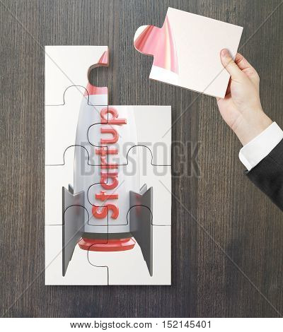 Close up of hand adding last piece to rocket ship puzzle on dark wooden background. Project start up and development process. 3D Rendering