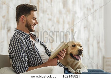 happy smiling man reading book to his dog on the couch