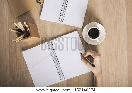 Top view of woman's hand writing in blank spiral notepad placed on wooden desktop with pencils and coffee cup. Mock up