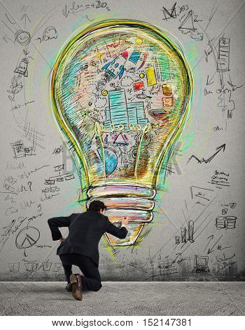 Businessman draws on the wall a big colored bulb with bright colors and business sketches