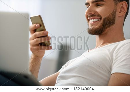 man with toothy smile looking into the smartphone, close up