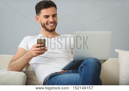 happy guy with smartphone smiling in front of laptop