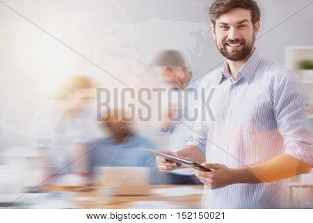 International connection. Handsome lively man is standing with tablet on background of blurred people and worldwide network.