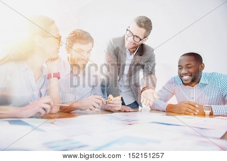 Effective work. Group of young smiling office workers are having meeting in modern light office.