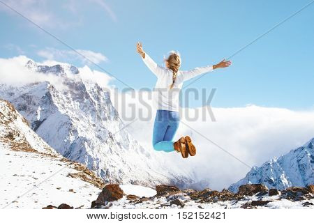 Unrecognizable young woman jumping on top of the mountain over blue skies, freedom and joy, winter season with snow