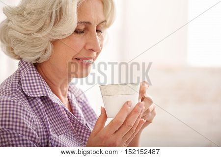 Happy old woman is enjoying hot coffee at home. She is sitting and smiling