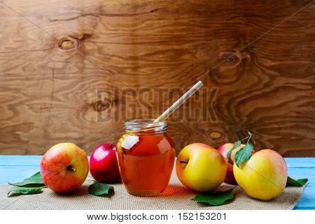 Glass honey jar with dipper and fresh apples copy space. Rosh hashanah concept. Jewesh new year symbols.
