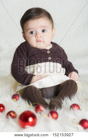 Baby girl in her first Christmas on a hair carpet with christmas balls and lights