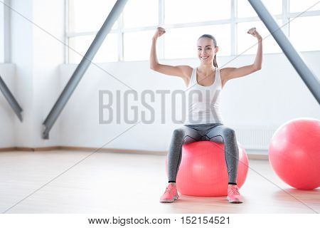 Result of intensive workouts. Delighted slim young woman showing her muscles and smiling while sitting on a pink fitness ball
