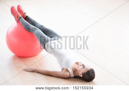 Having a workout. Attractive slim well built woman resting her legs on a fitness ball and holding her body up while having fitness training